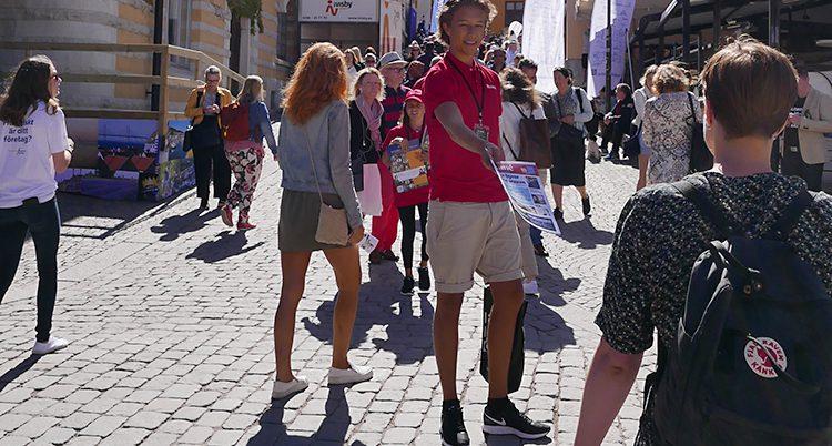 En kille delar ut en tidning på gatan i Visby