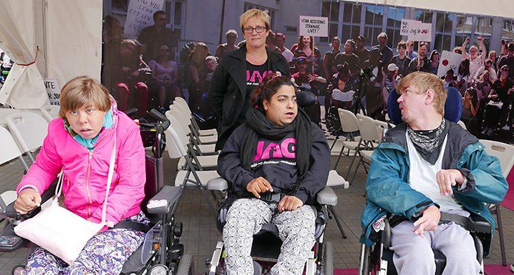 En äldre kvinna står bakom tre ungdomar i rullstol.