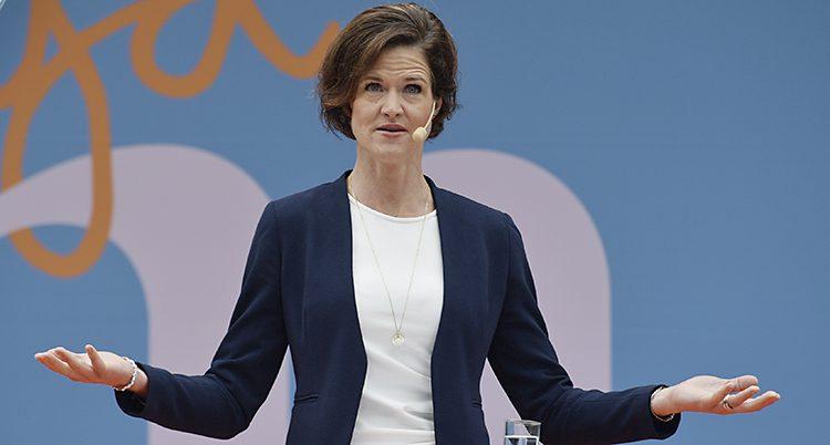Moderaternas ledare Anna Kinberg Batra framför en blå vägg med ett stort M