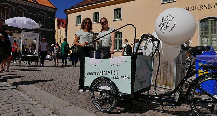 De står framför en cykelkärra med texten: Bli inte medrasist