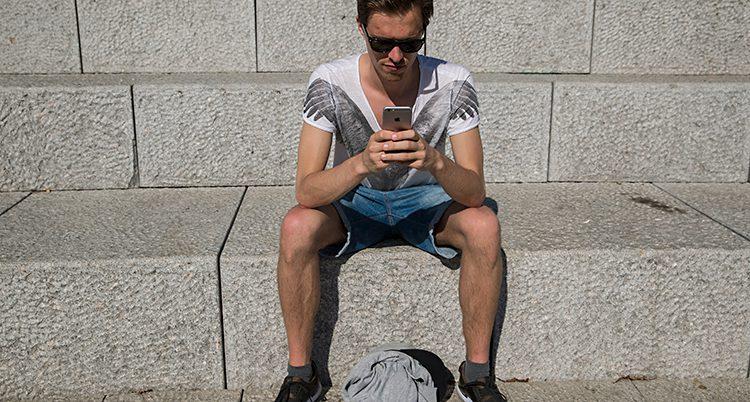 En kille i sommarkläder stirrar i en mobil
