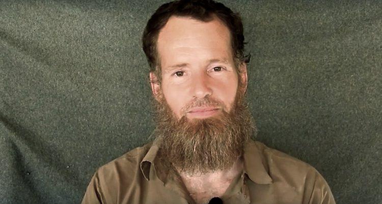 Stephen McGown sitter i en brun skjorta som är uppknäppt i halsen, den ser lite oordnad ut. Han har ett blekt ansikte, mörkt hår och ett ljusbrunt ganska långt och ovårdat skägg. Bilden är tagen under fångenskapen.