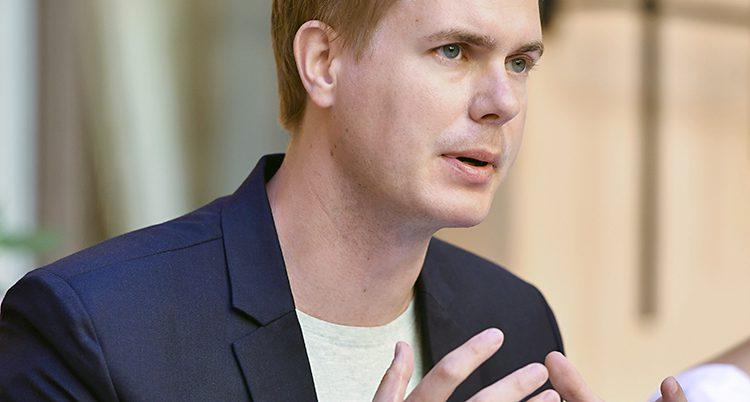 En bild på Gustaf Fridolin i vit t-shirt under en blå kavaj.