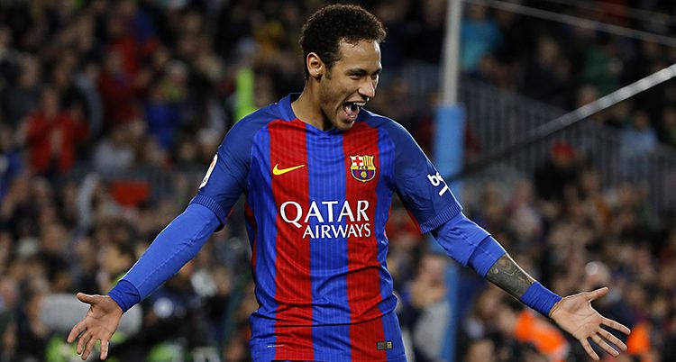 Neymar i Barcelonas rödblå-randiga tröja står på fotbollsplanen och ser glad ut. Han slår ut med händerna.