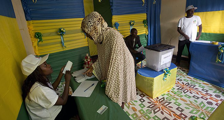 En kvinna i sjal står vid ett bord för att rösta.