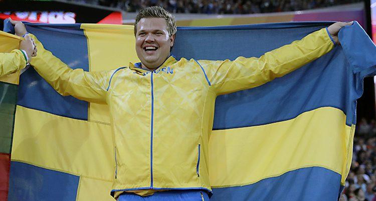 Daniel Ståhl skrattar och håller upp en svensk flagga.