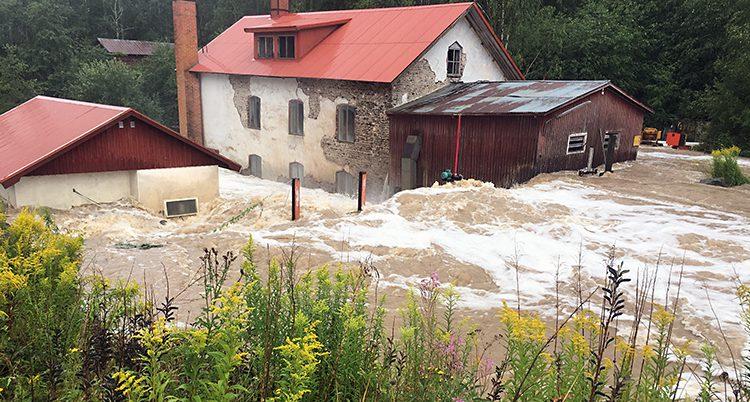 Vatten virvlar runt ett hus.