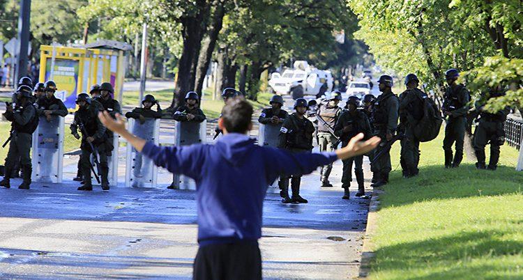 En man i blå jacka med ryggen mot fotografen sträcker ut sina armar mot poliser i skyddskläder som står framför honom.