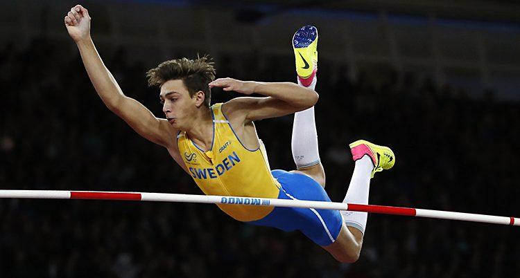 Armand Duplantis i sin gula tröja och blå shorts river hindret. Bilden är tagen när Armand är i luften och just har rivit.