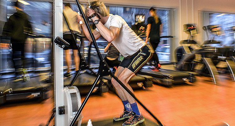 En man står upp och tränar vid en maskin.