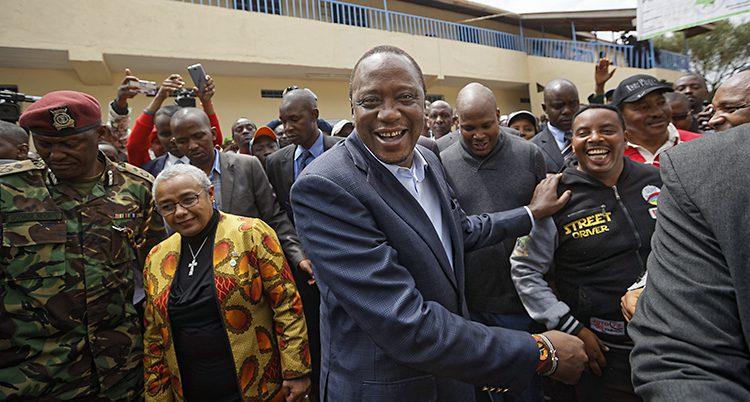 Presidenten skakar händer efter valet. Han tittar in i kameran och ser glad ut.
