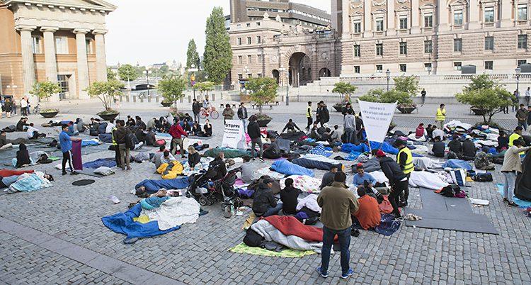 människor i sovsäckar sitter på marken på Mynttorget nära riksdagen i Stockholm.