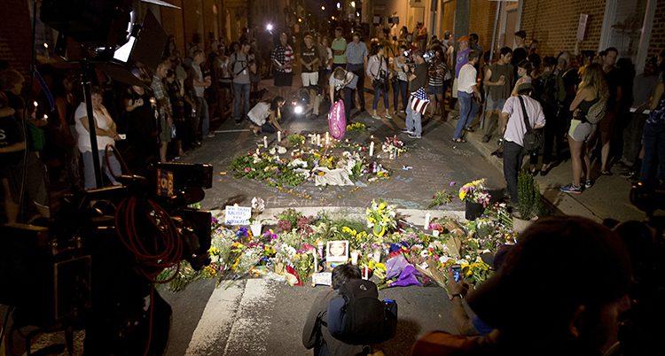 Människor har samlats på en gata. I mitten står massor av blommor.
