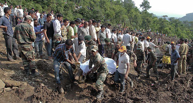 Massor av människor står i leran i en brant backe. Några personer i förgrunden bär på en övertäckt kropp.