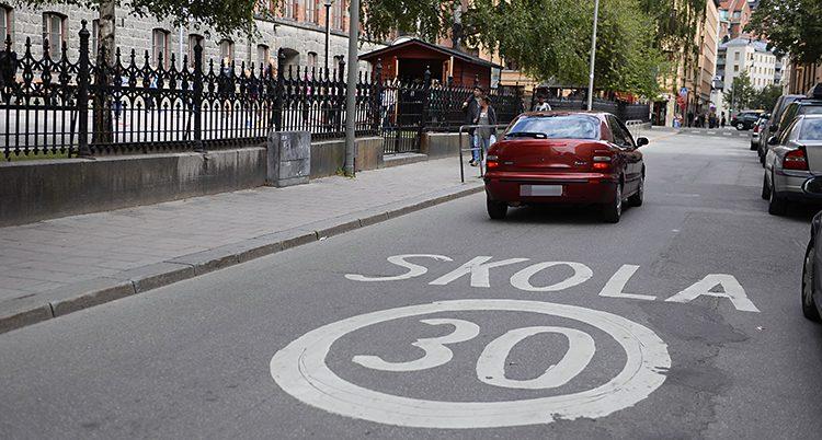 En bil kör förbi en skola. På gatan är markerat att det är 30 km i timmen som gäller som hastighet.