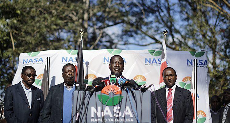 Raila Odinga står vid en talarstol. Två män står på varsin sida om honom.