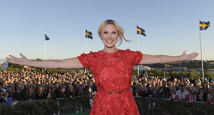 Sanna Nielsen i röd klänning står på scenen på Skansen. Hon sträcker ut armarna åt sidorna och ser glad ut. Bakom henne ser man publiken, en blå himmel och två svenska flaggor som vajar.
