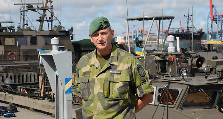 Thomas Olsson står i kamouflagekläder och grön basker. Han här händerna bakom ryggen. Bakom honom ser man en båt.