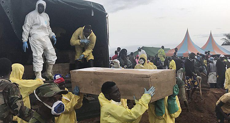 Människor lyfter ut en kista ur en lastbil