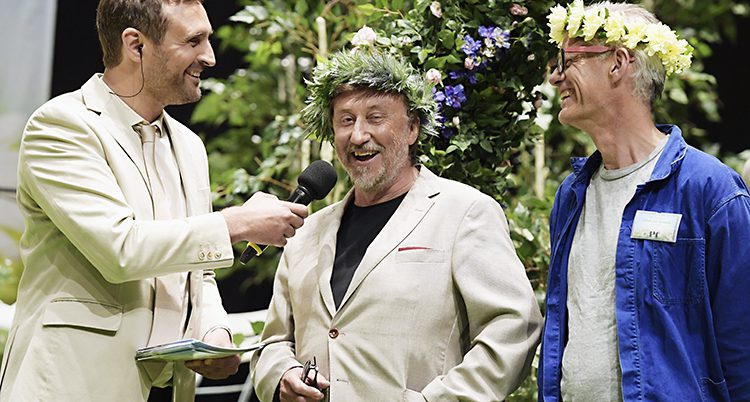 Janne Josefsson med krans på huvudet blir intervjuad