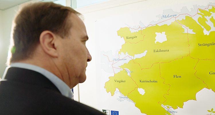 Stefan Löfven tittar på en karta över Sverige.