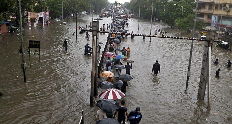 En bild på en vattenfylld gata i Indien. Bilden är tagen ovanifrån. En rad med människor vadar i vattnet. Man ser deras uppfällda paraplyer.
