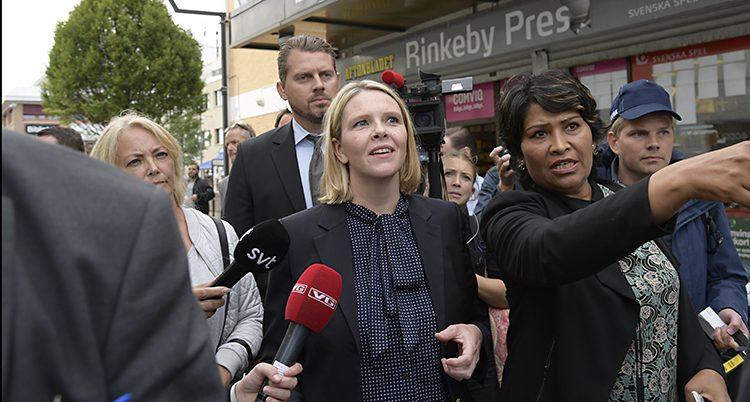 Sylvi Listhaug står i Rinkeby. Runt omkring henne står medarbetare och journalister.