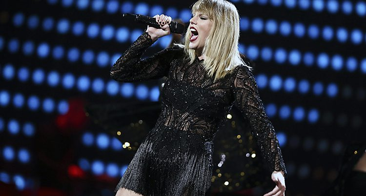 Taylor Swift klädd i svart sjunger på en scen.