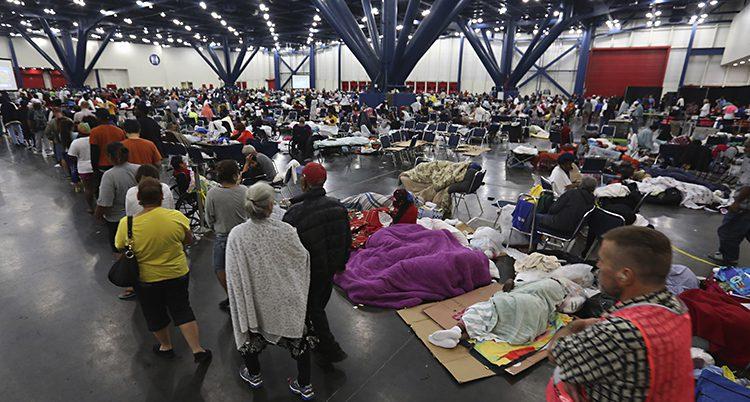 Folk köar för att få mat i en stor lokal. Bredvid kön ligger folk och vilar i sovsäckar på golvet.
