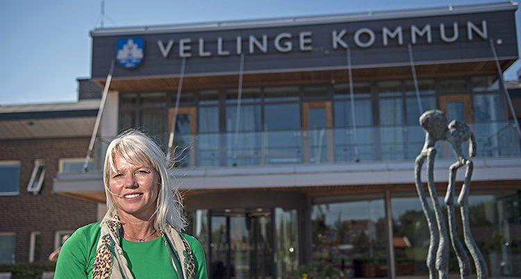 Kommunens ledare Carina Wutzler står framför kommunhuset i Vellinge. Hon har grönt på sig och ler.