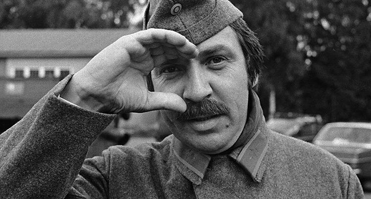 En svartvit bild på Janne Carlsson klädd i soldatkläder. Fotot är från filmen Repmånad.