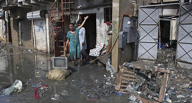En man står vid sitt översvämmade hus.