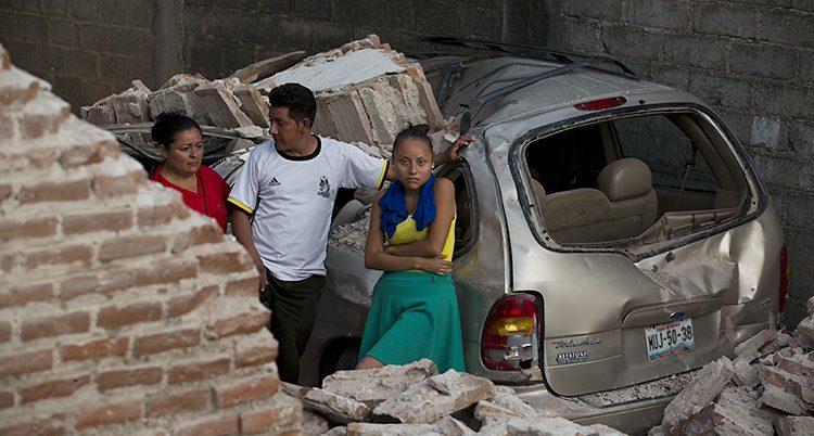 En familj vid sitt rasade hus.
