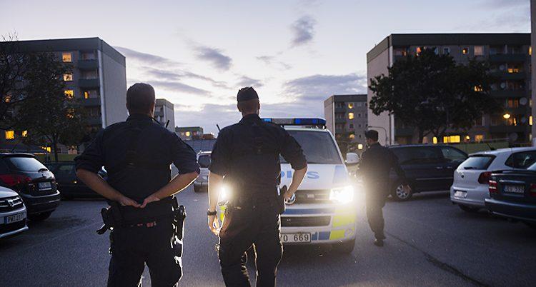 Två poliser står och tittar mot en gata.