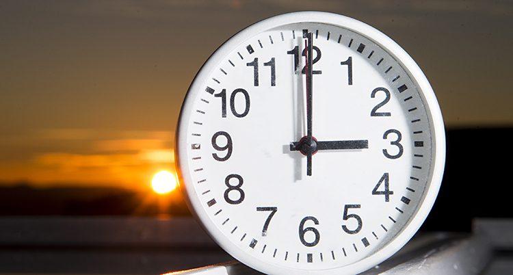 En klocka framför en sol som håller på att gå ner.