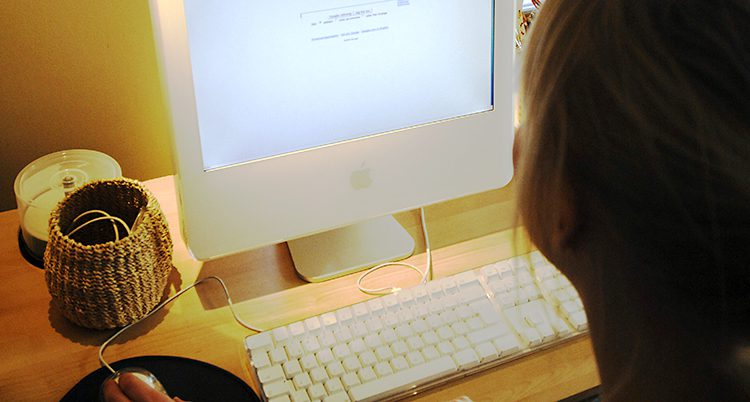 En datorskärm med ett tangentbord. En kvinna sitter vid datorn.