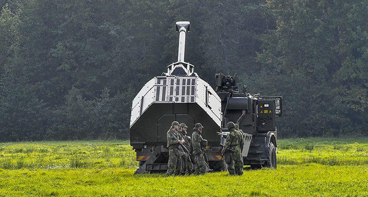 En svensk pansarvagn med soldater bredvid.