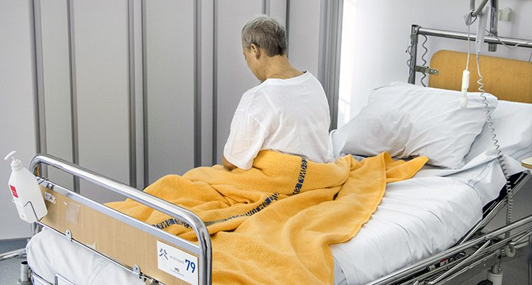 En sjuk kvinna i en sjukhussäng.