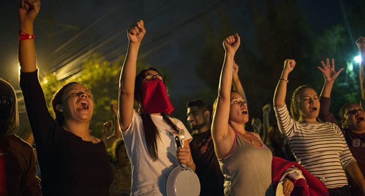 Människor skriker protester och sträcker upp knutna nävar