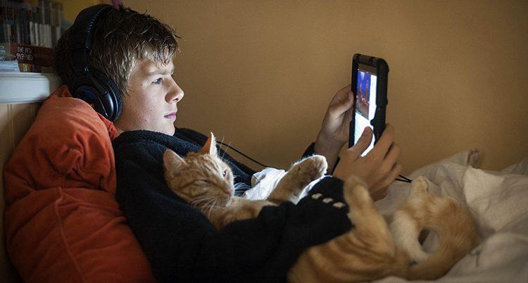 En kille ligger i en säng och tittar på en film i en iPad.
