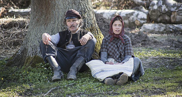 De två programledarna har gammeldags kläder och sitter på marken.