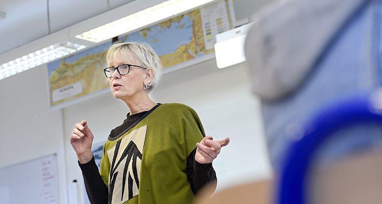 En lärare i grön tröja står längst fram i ett klassrum