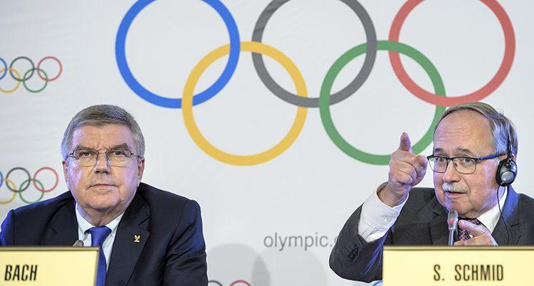Två äldr män vid ett bord. OS-ringarna på väggen bakom.