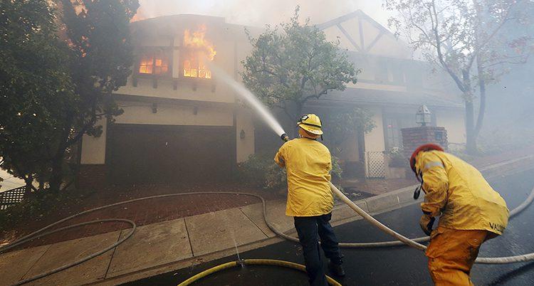Två brandmän sprutar vatten på ett brinnande hus.