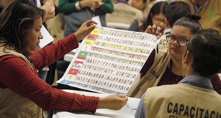 En kvinna håller upp en lista vid valet.