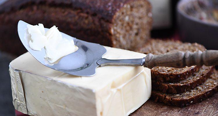 Ett mörkt bröd med en ost framför.