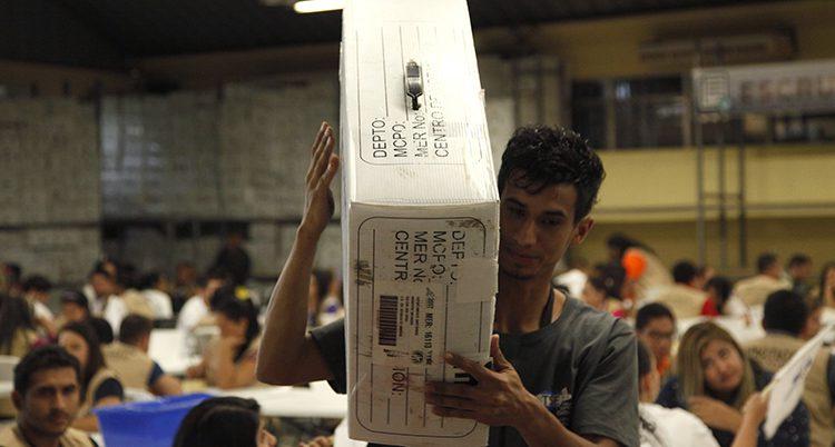 En man med en stor, vit låda på axeln
