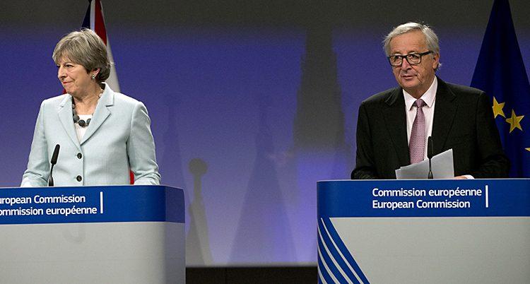 May och Juncker står i varsin talarstol och ser nöjda ut