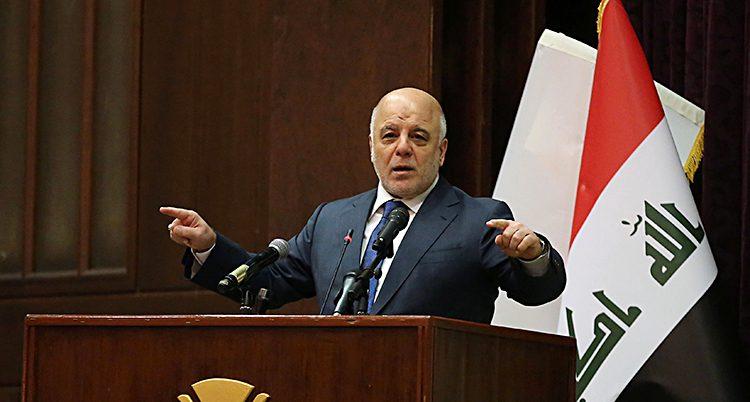 Iraks ledare Haider al-Abadi står vid en talarstol och talar.