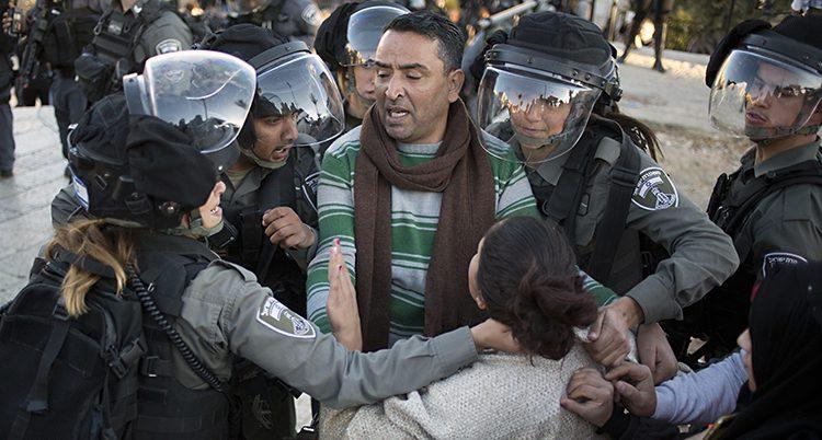 Poliser från Israel knuffar bort en palestinier.